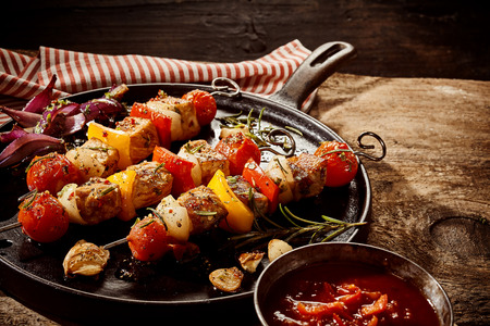Single round black cast iron frying pan filled with seasoned kebabs on sticks with garlic, onion and rosemary next to cup of chili sauce over rustic wooden table
