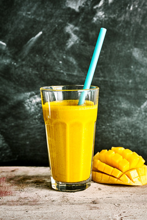 energising: Delicious tropical mango smoothie blended with yogurt served with a straw in a tall glass with a fresh hedgehog cut mango alongside on a rustic table