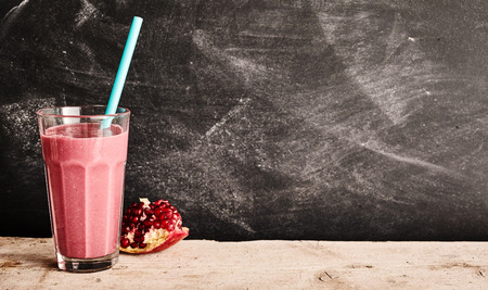 energising: Healthy pomegranate and yogurt smoothie rich in vitamin c and dietary fiber with fresh fruit alongside on a rustic table with copy space on an old slate chalkboard Stock Photo