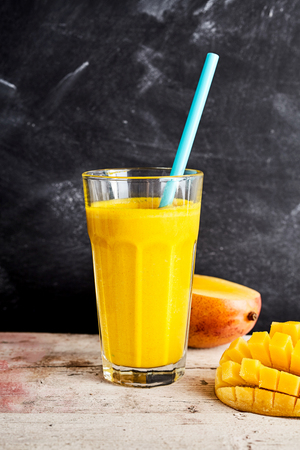 pip: Fresh mango smoothie on a rustic counter served with a halved fresh fruit on the pip and decorative hedgehog cut portion in the foreground for a healthy tropical summer drink