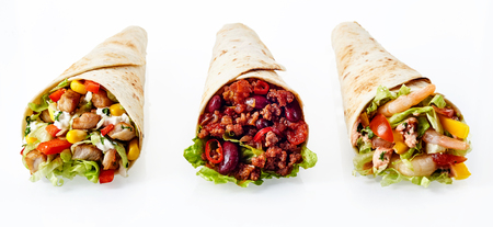 wraps: Primer plano Naturaleza muerta del Trío de Tex Mex Fajita Wraps envueltos en la parrilla Tortillas de Harina y lleno de variedad de rellenos como el pollo, el chile y camarones y verduras frescas en el fondo blanco