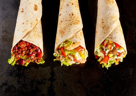 High Angle Still Life of Trio of Tex Mex Fajita Wraps on Black Background - Variety of Grilled Flour Tortilla Wraps Stuffed with Different Fillings Such as Chicken and Chili Imagens - 54347210