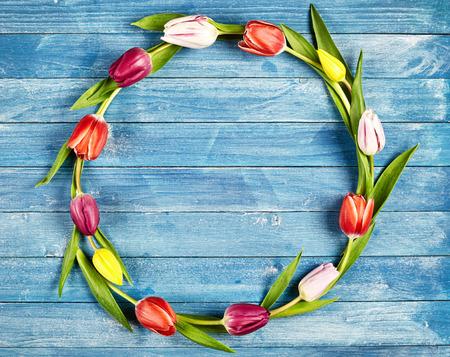 Rund Rahmen von bunten Frühling Tulpen auf einem blauen Holz Hintergrund mit zentralen Kopie Raum