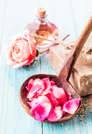 blue petals: Close Up of Pink Rose Petals in Rustic Wooden Ladle in Spa Themed Still Life with Blue Painted Wooden Background with Handmade Soap, Delicate Pink Rose and Bottle of Essential Aromatic Oil Stock Photo