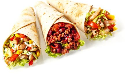 Nahaufnahme Stillleben von Trio von Tex Mex Fajita Wraps Wrapped in Grilled Tortillas und gefüllt mit Vielzahl von Füllungen wie Huhn, Chili und Garnelen und frischem Gemüse auf weißem Hintergrund
