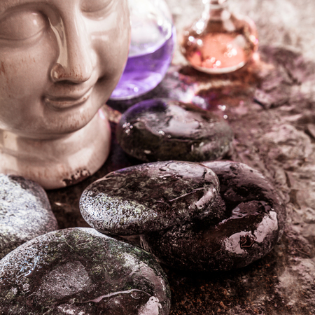 ambiente: Zen Spa Themed Still Life of Buddha Head Bust and Bottles of Aromatic Essential Oils Amongst Smooth Wet River Rocks with Copy Space