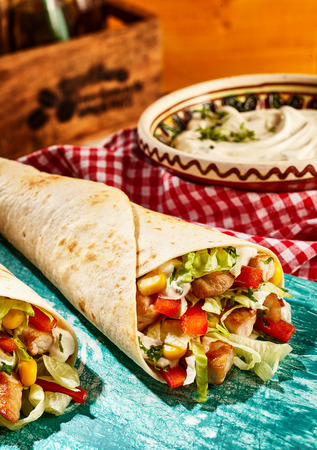 tex: Close Up Still Life of Chicken Fajitas Stuffed with Fresh Vegetables and Resting on Worn Blue Cutting Board on Table with Condiments and Dressings in the Background - Tex Mex Mexican Meal
