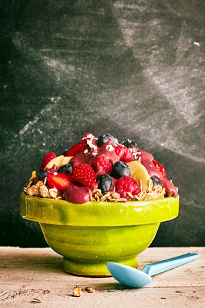 shreds: Scrumptious acai berry bowl of cereal overflowing with blueberries, slices of bananas, strawberry and coconut shreds next to blue spoon on old wooden table Stock Photo