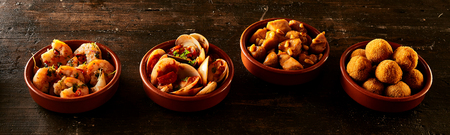 croquettes: Row of fried croquettes, shrimp, clams and nuts covered in sauce as part of a traditional Spanish cuisine Stock Photo