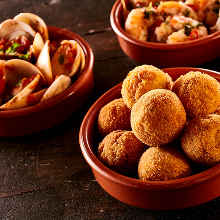 croquettes: Codfish bacalao croquettes covered in bread crumbs and fried served with steamed spicy Venus shell clams in individual bowls for Spanish tapas Stock Photo