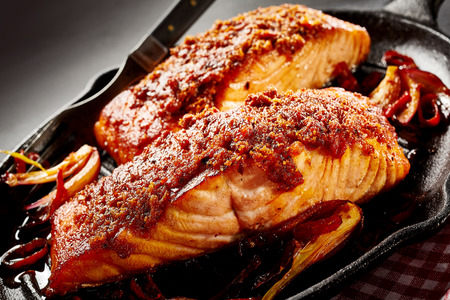 ovenbaked: Close up of baked salmon dish for one serving next to fork in black cast iron pan Stock Photo