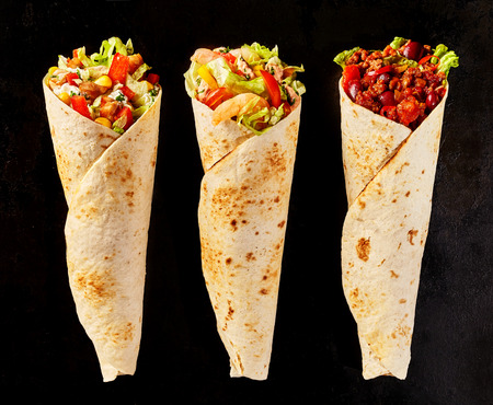 tex: High Angle Still Life of Trio of Tex Mex Fajita Wraps on Black Background - Variety of Grilled Flour Tortilla Wraps Stuffed with Different Fillings Such as Chicken and Chili