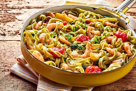 Изысканный морепродуктов Итальянская паста тальятелле с креветками, помидорами, шпинатом и чесноком, подается на деревенский деревянный стол в желтой сковороду, высокий угол зрения Фото со стока