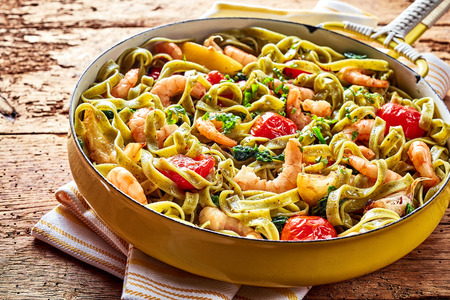 Gourmet seafood Italian tagliatelle pasta with shrimp, tomato, spinach and garlic served on a rustic wooden table in a yellow frying pan, high angle view Фото со стока