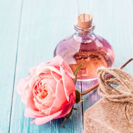 spa flower: Close Up of Delicate Pink Rose Flower on Blue Painted Wooden Background with Handmade Soap, Twine and Small Bottle of Essential Aromatic Oil with Cork Stopper in Spa Themed Still Life with Copy Space