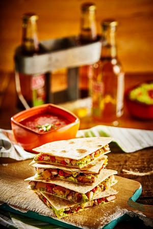 quartered: Stack of four scrumptious wheat tortilla quesadillas on cutting board in front of salsa, beer and guacamole with napkin