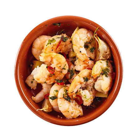 spanish tapas: Spicy shrimp tails garnished with herbs served in a bowl for traditional Spanish tapas, overhead view on white in square format