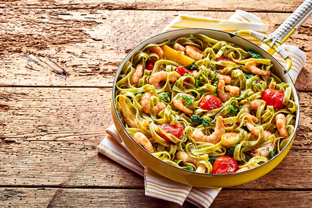speciality: Speciality Italian tagliatelle seafood pasta with shrimp or prawn tails, tomato, spinach and garlic served in a rustic restaurant in a yellow frying pan, high angle view with copy space