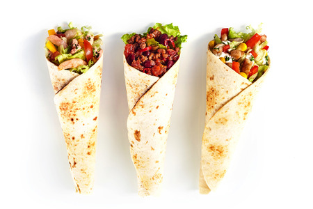 tex: High Angle Still Life of Trio of Tex Mex Fajita Wraps Wrapped in Grilled Flour Tortillas and Filled with Variety of Fillings Such as Chicken, Chili and Shrimp and Fresh Vegetables on White Background
