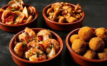 croquettes: Four round ceramic red bowls of Spanish appetizers knowns as tapas with seafood, nuts and sauces