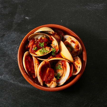 top down: Top down view of single round red bowl of venus shells and delicious sauce as a Spanish style appetizer
