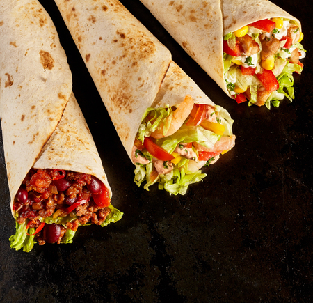 tex mex: High Angle Still Life of Trio of Tex Mex Fajita Wraps on Black Background - Variety of Grilled Flour Tortilla Wraps Stuffed with Different Fillings Such as Chicken, Shrimp and Chili - with Copy Space