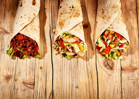 Front view of three meat, bean and vegetable stuffed burritos in baked wheat tortillas on old wooden table table