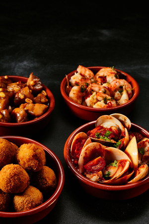 Four round ceramic bowls of delicious traditional Spanish tapas on black background