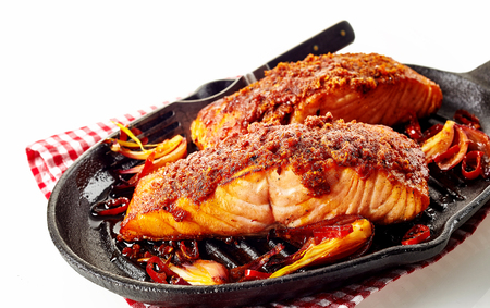 Nutritious baked salmon pieces with marinated seasoning in black pan over checkered napkin on white surface Фото со стока