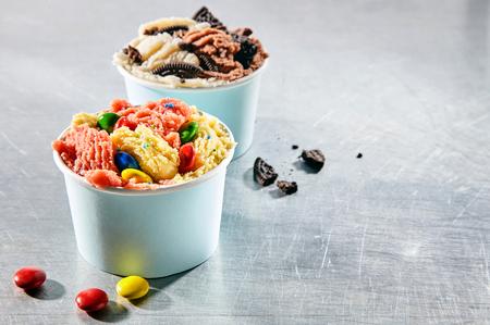 Dos postre saca los envases rellenos con crema de helado italiano congelado cubierto con trozos de caramelo y galletas cumbles Foto de archivo - 54712574