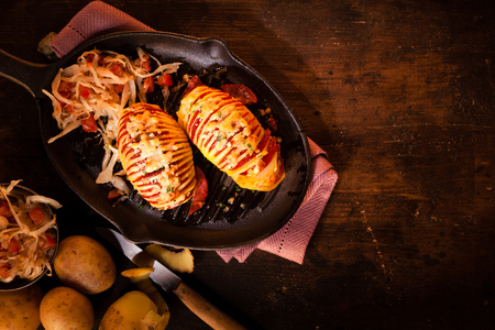 alternating: Gourmet baked potatoes sliced through with alternating slices of tomato and potato topped with grilled melted cheese and served with fresh salad, high angle view Stock Photo
