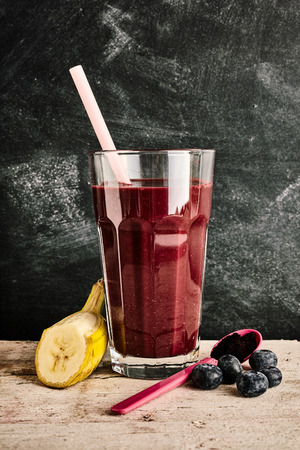 acai berry: Single tall glass of delicious acai berry smoothie in between a slice of banana, blueberries and plastic spoon over marble background