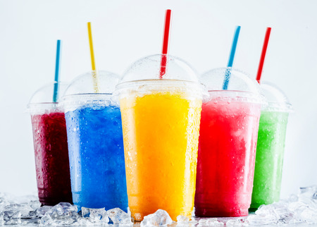 Still Life Profile of Frozen Fruit Slush Granita Drinks in Plastic Take Away Cups with Lids and Drinking Straws Chilling on Cold Metal Surface with Scattered Ice Cubes