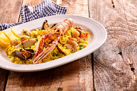 langoustine: Delicious Spanish recipe of cooked yellow pasta garnished with lemon peel, peas and lobster in oval plate under checkered napkin and wooden table with copy space