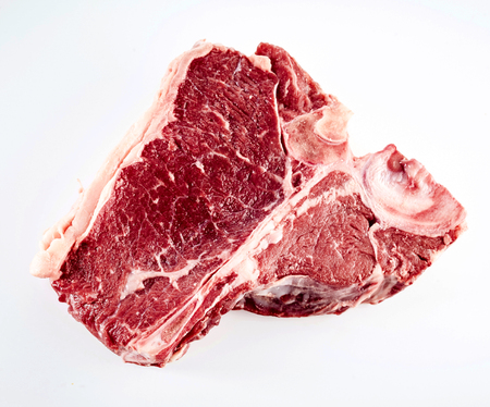 porterhouse: Raw beef porterhouse steak for grilling or barbecuing viewed close up high angle isolated on white