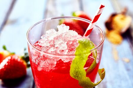 slush: Single close up of delicious red ice slush beverage with straw and peel of lime hanging on the side Stock Photo