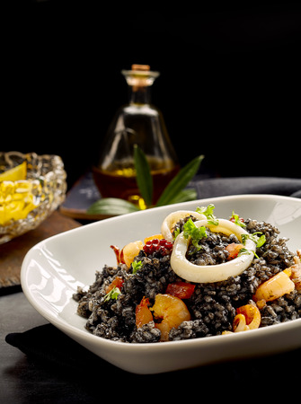 prepared dish: Close view of prepared Catalonian arroz negro dish with bottle of olive oil and lemons in background