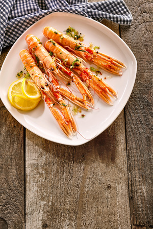 langoustine: High Angle Still Life of Four Cooked Langoustine Shellfish Arranged on Modern White Platter with Lemon Slices and Herbs Resting on Rustic Wooden Table with Checkered Cloth Napkin and Copy Space Stock Photo