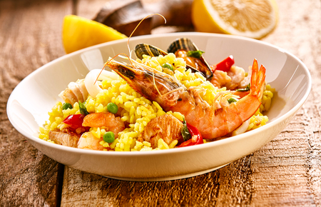 vermicelli: Close Up Still Life of Traditional Paella Dish with Fresh Seafood - Prawns and Shellfish - Served on Yellow Rice in White Bowl with Fresh Lemon on Rustic Wooden Table