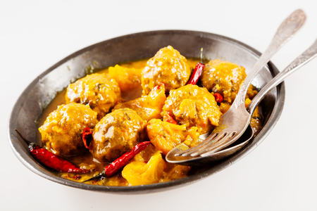 smothered: Close Up of Traditional Tajine Berber Dish of Meatballs Smothered in Spicy Yellow Curry Sauce with Hot Red Peppers and Served in Shallow Bowl with Cutlery on White Background