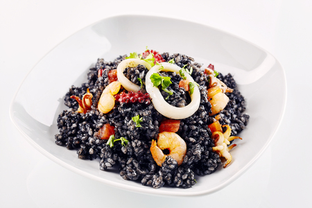 prepared dish: Close up of freshly prepared Arroz Negro garnished with various types of seafood in white dish