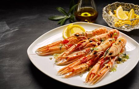 catering food: Serving of four lobsters garnished with sauce and lemon peel cooked and served on square plate over black table next to bottle of olive oil