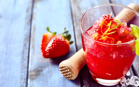 slush: Delicious zesty strawberry ice slush drink with lime peel and strawberry beside wooden crusher on table