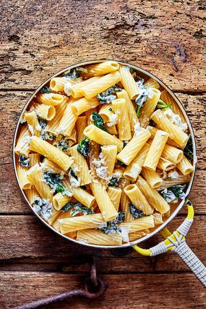 시금치와 파 르 마 치즈 강판 리코 이탈리아어 국수 나 파스타 조리법은 소박한 테이블, 건강한 전채 냄비에 오버 헤드보기를 제공