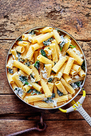Ricotta Italian noodles or pasta recipe with spinach and grated parmesan cheese served in a pan as a healthy appetizer, overhead view on a rustic table