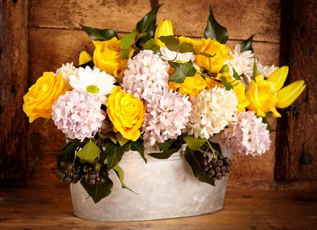 arreglo floral: hermosas flores blancas y amarillas clasificadas en olla de metal viejo sobre el fondo interior rústico Foto de archivo