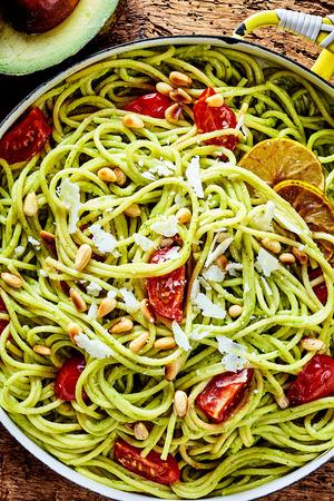 pinoli: Delizioso antipasto pasta italiana con pera avocado, pomodori freschi, pinoli e parmigiano in un vicino vista dall'alto in una padella