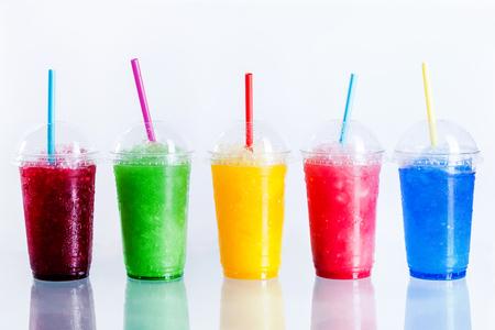 Панорамный Натюрморт Красочные Замороженные фрукты слякоти Granita Напитки в пластиковые вынос Чашки с крышками и соломинки для питья в передней части белый фон