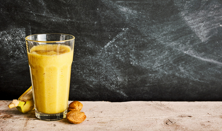 energising: Healthy banana and almond smoothie served in a tall glass with fresh ingredients alongside on a rustic table with slate background and copy space