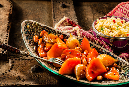 raisins: Still Life of Traditional Tajine Vegetable Dish Made with Bright Orange Vegetables in Sauce and Served in Long Narrow Modern Dish with Fork on Rustic Wooden Table with Couscous